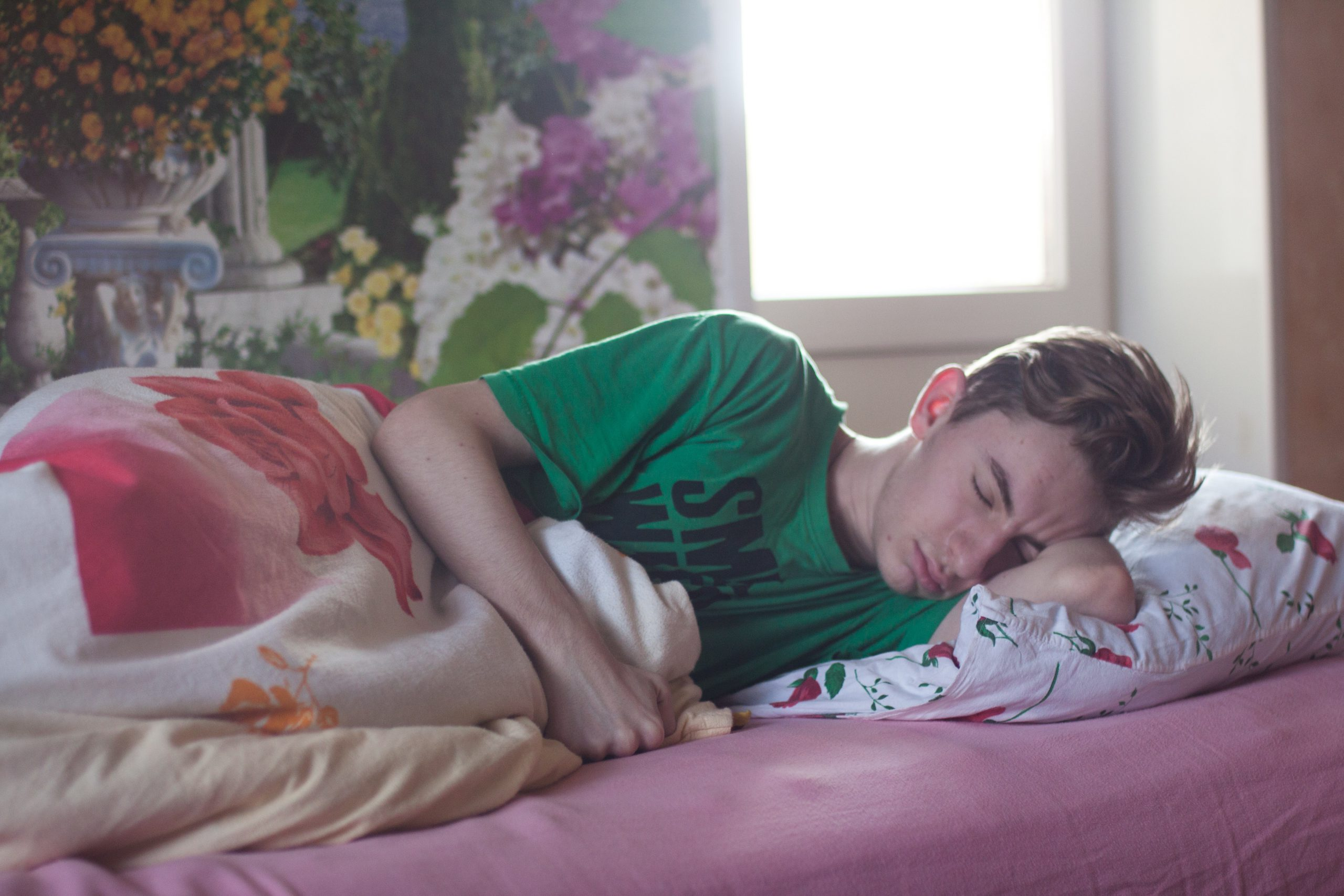 man-wearing-green-printed-crew-neck-shirt-while-sleeping-296817